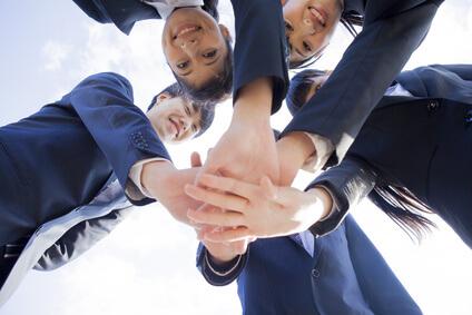 男女5人が手を重ねている