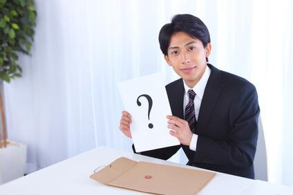 「?」が書かれている紙を持った男性