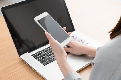 スマートフォンを持ってパソコンを触る女性